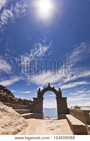 arch above titicaca lake in peru with blue sky and sky shining