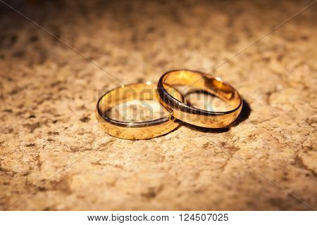 Wedding gold rings on the stone. In the rays of yellow light.