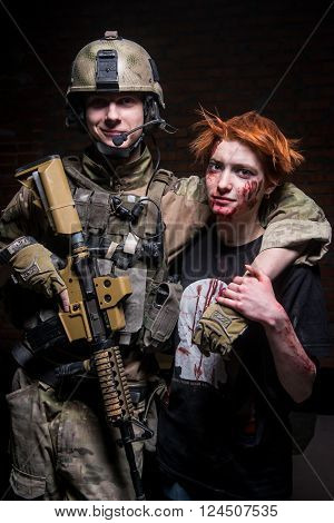 KIEV,UKRAINE - February 20 :Soldier with gun and zombies with bloody face during a thematic game about zombies in Kiev,Ukraine on February 20,2016.