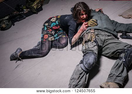 KIEV,UKRAINE - February 20 : Zombie girl with bloody face lies near  man body during the quest game in zombie theme in Kiev,Ukraine on February 20,2016.