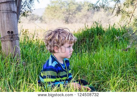 Small pensive boy in rural long grass next to fence pole