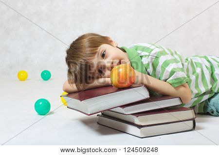 A boy of six years old is laying on a pile of books and observing an apple.White background