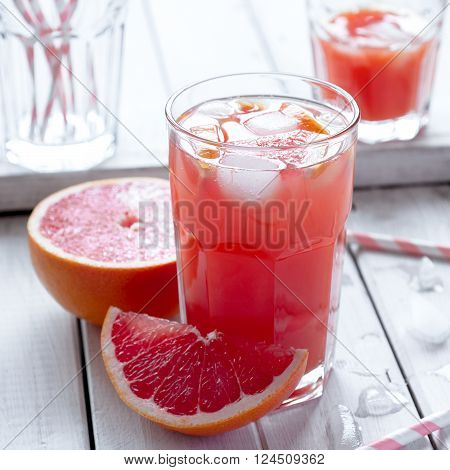 Fresh grapefruit juice with fruits and crushed ice in glasses selective focus