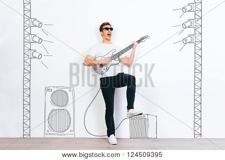 Rock star! Young handsome man playing drawn guitar and keeping mouth open while standing against white background with illustration of stereo column and stage light