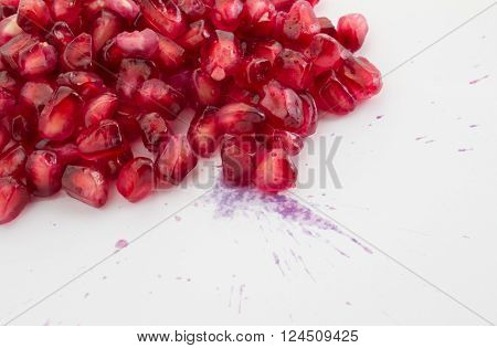 Close up photo of pomegranate seeds isolated on white with juice splatter