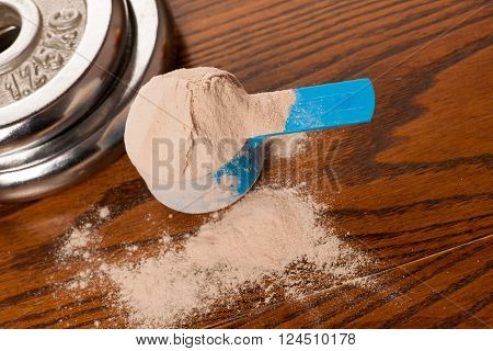 Whey Protein Powder In Measuring Scoop And Dumbbell On Wooden Background.