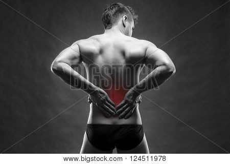 Kidney pain. Man with backache. Handsome muscular bodybuilder posing on gray background. Black and white photo with red dot