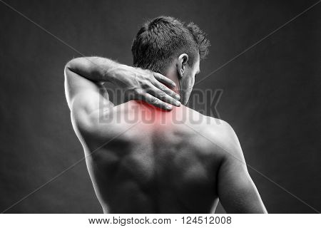 Pain in the neck. Man with backache. Muscular male body. Handsome bodybuilder posing on gray background. Black and white photo with red dot