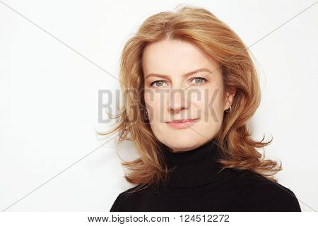 Portrait of beautiful happy smiling mature woman with curly hair and clean make-up