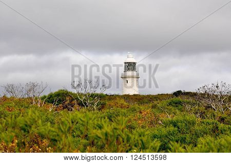 Cape Naturaliste Lighthouse in the coastal vegetated dune on the Leeuwin-Naturaliste ridge in Dunsborough, Western Australia under stormy skies.