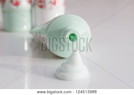 Squirt of cosmetic cream next to an open tube