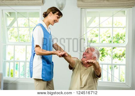 Smiling happy nurse assisting senior man at health club