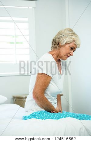 Tensed senior woman sitting on bed at home