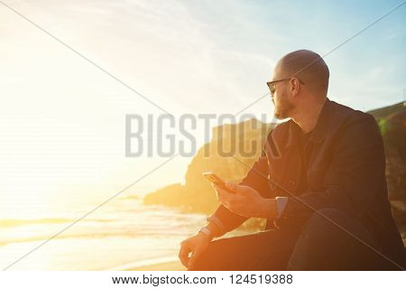 Young hipster man traveler with cell telephone in hand is enjoying amazing landscape while is sitting on the beach near ocean with copy space background for your text message or advertising content