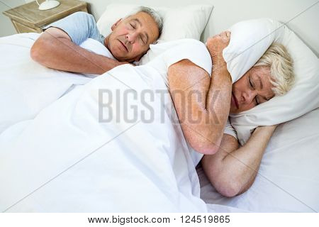 High angle view of senior woman sleeping by snoring man on bed at home