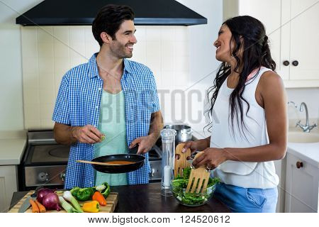 Young couple cooking food together in kitchen at home