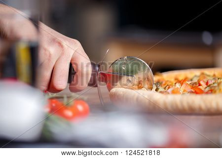 Slicing fresh pizza with pizza knife. Shallow dof. Focused on hand.