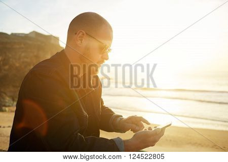 Young bearded hipster guy in fashionable sunglasses is watching photos on mobile phone what he took now during rest near sea with copy space background for your advertising text message or content