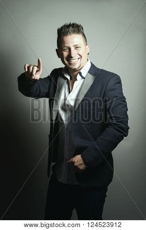 elegante smiling businessman with jacket greeting by pointing with finger