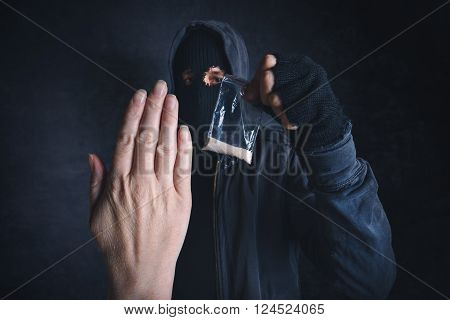 Saying No to drug dealer offering narcotic substance fight addiction unrecognizable hooded criminal offering drugs in dark street.