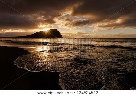Summer sunrise seascape on tropical island Tenerife, Canary in Spain. Playa de La Tejita beach view on atlantic ocean and Punta Roja rock.