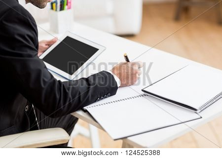 Businessman writing in a diary and using a digital tablet in office