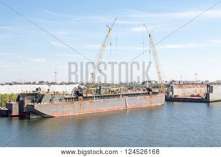 Construction cranes at a dry dock and shipyard