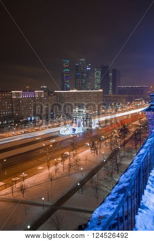 Arch of Triumph with illumination and skyscrapers far away at night in Moscow, Russia