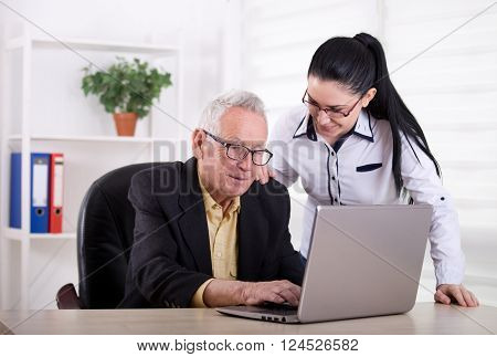 Senior Man And Young Woman Looking At Laptop