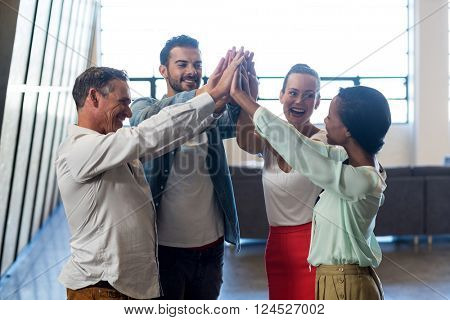 Business colleagues doing high five in the office