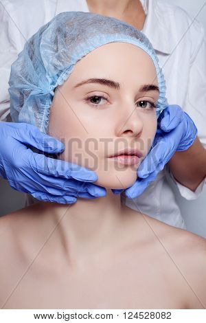 Beauty Woman face surgery close up portrait. Female model. studio shot beauty octor in the background, Plastic surgery touching the head of a female face blue medical gloves