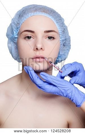 Attractive young woman gets cosmetic injection, an injection in the upper lip, over white background. Doctors hands making an injection in face, close-up. Beauty Treatment.