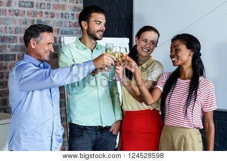 Colleagues toasting champagne flutes in office