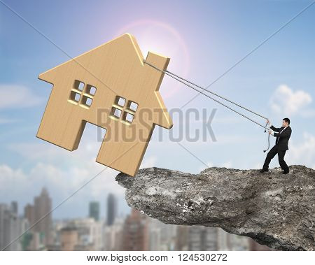 Man Pulling Rope To Move Wooden House On Cliff Edge