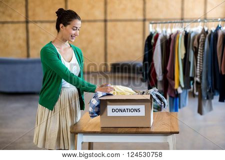 Young woman sorting clothes from donation box in the office