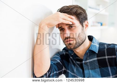 Depressed man leaning on wall at home