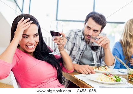 Man looking drunk woman with wine glass at home