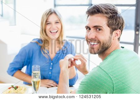 Man gifting finger ring to his woman at home