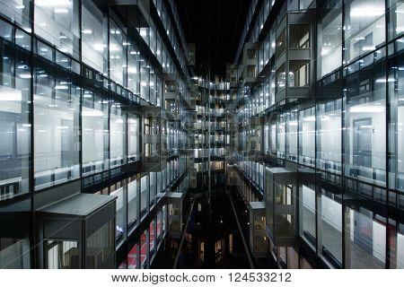 Beautiful illuminated windows of modern building at night in city