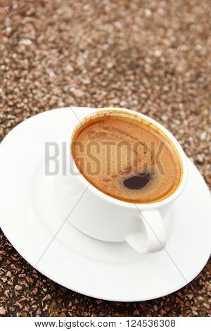 Close-up of white cup of coffee with foam on a stone table