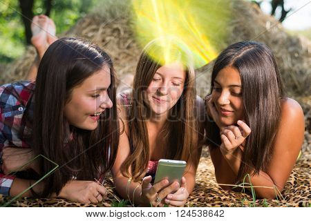 Three teenage girls using mobile smart phone outdoors on hay stack summer outdoors background