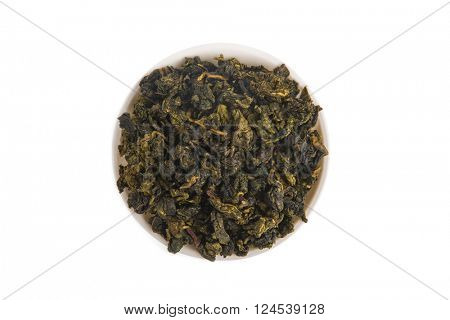 Top view of Tie Guan Yin Oolong tea on white porcelain container, isolated on white background
