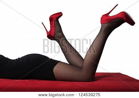 female lying on a red sofa with legs up in the air wearing red heels on white background