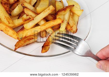 fried potatoes on a glass plate with fork
