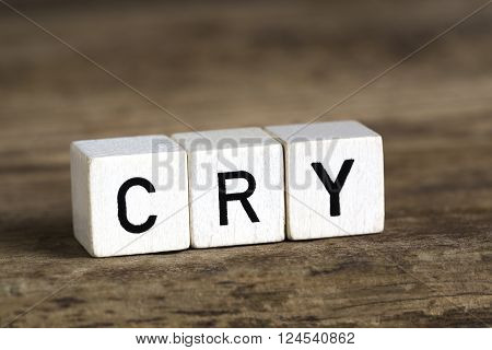 The word cry written in cubes on wooden background