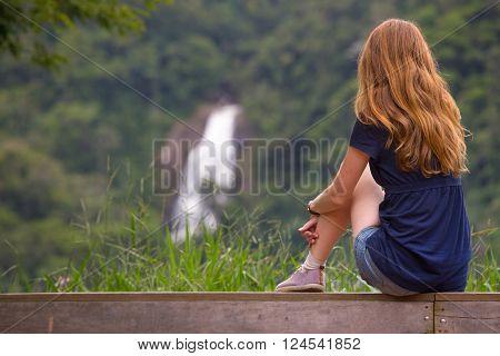girl sitting on the bench and waterfall at the background cachoeira do pacau santa rita de jacutinga Brazil
