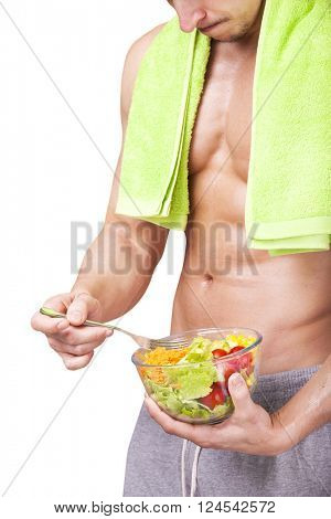 Fit young man holding a bowl of salad, isolated on white background