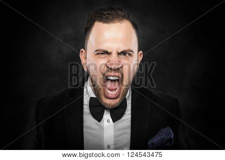 Angry businessman shouting or screaming over dark background.