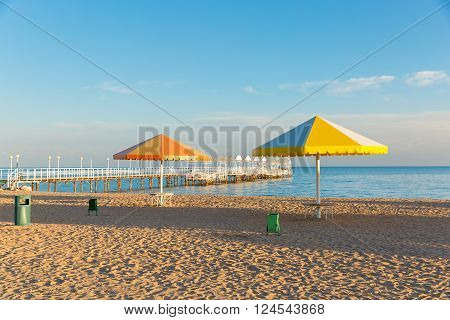 Beach at the sea with the umbrellas. Pier
