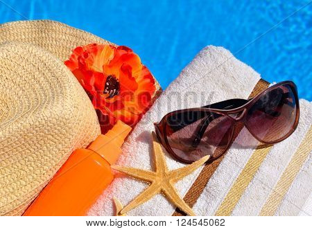 Beach hat sunglasses bath towel sun spray starfish near the swimming pool
